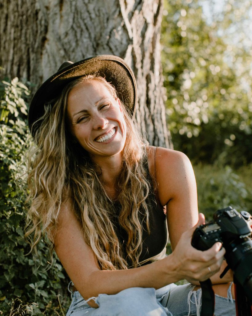 Woman is smiling while laughing and holding a Cannon DSLR camera. She is sitting down with her back against a tree and the setting sun is highlighting the side of her face and hair.