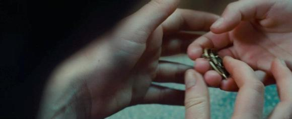 Movie Still: Prim Gives Mockingjay Pin To Katniss