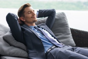 man wearing  a suit and laying on sofa