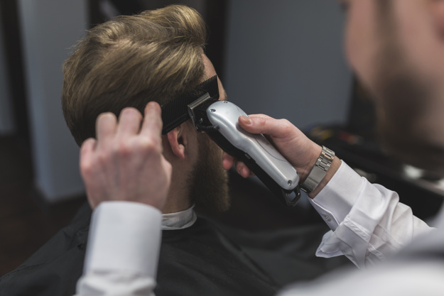 hairdresser giving haircut to man