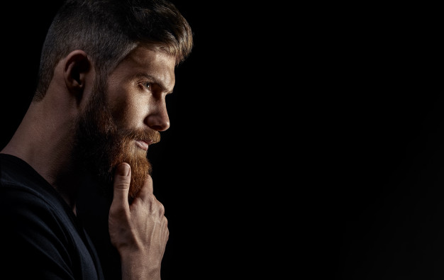 attractive-pensive-young-bearded-man-looks-into-distance