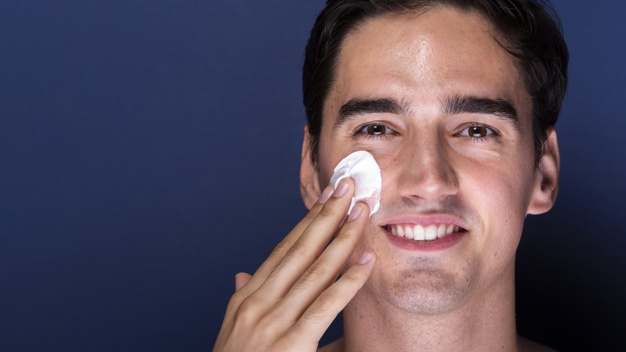 man using skin care products on face