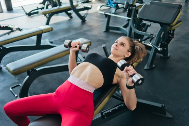 fit-young-woman-doing-dumbbell-press-lying-down-inclined-bench-gym