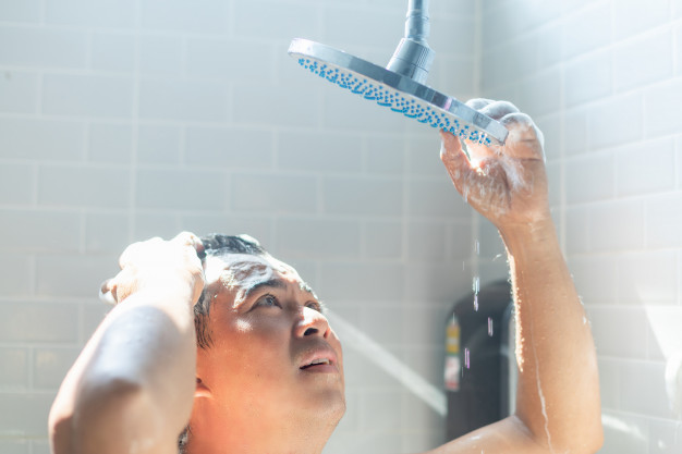 man in shower confused between hot and cold shower