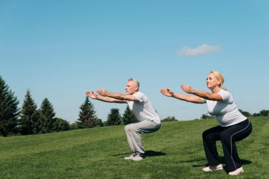 old couple doing squat exercise bodyweight
