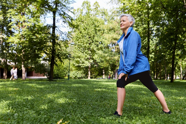 woman over 50s doing lunges in park