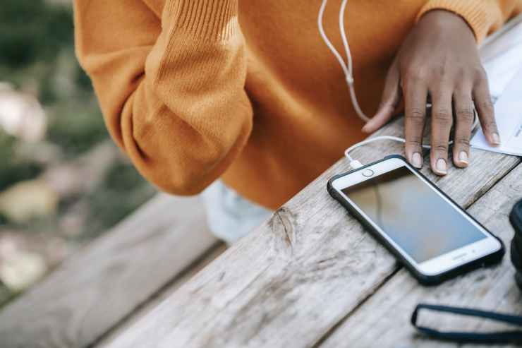 black woman with smartphone and earphones at table