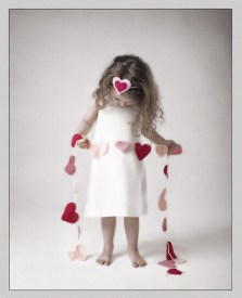 girl looking down at a string of crochet hearts