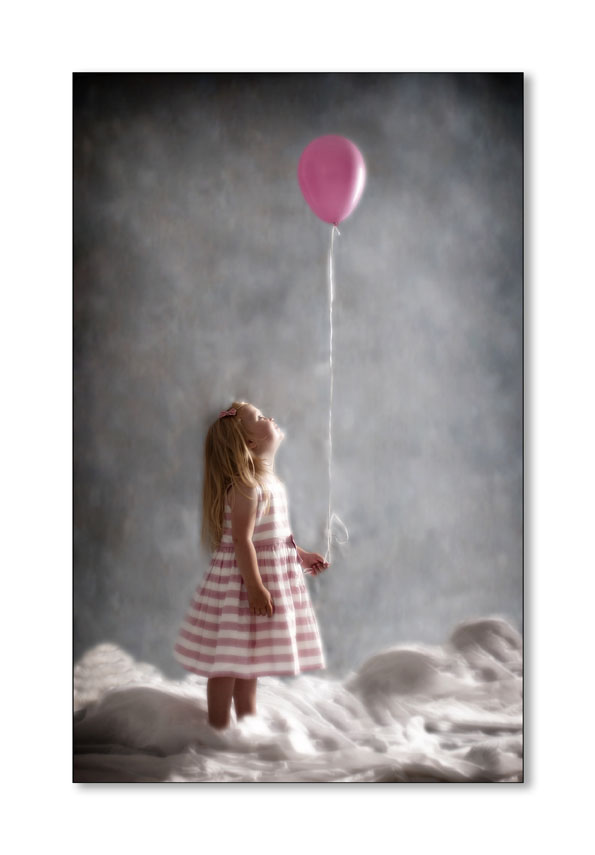 younggirl on a sea of clouds holding a pink ballon