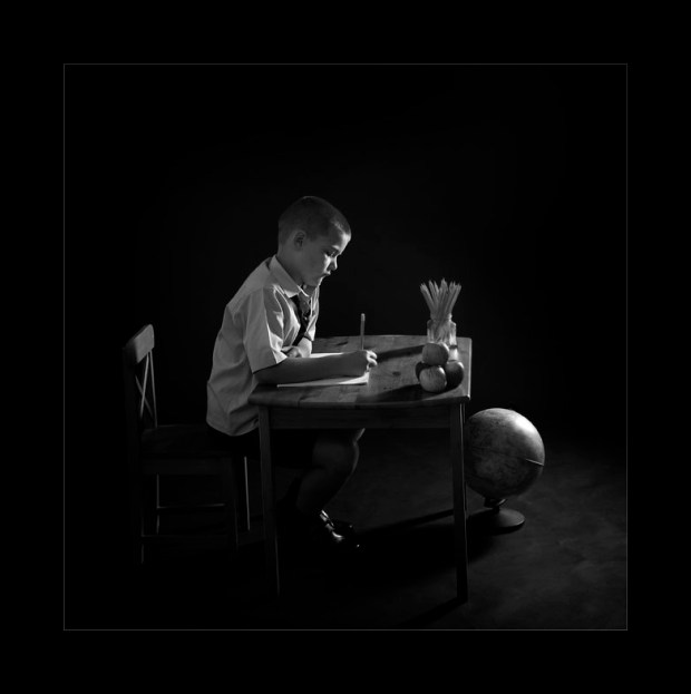 black and white image of boy in school uniform at a desk