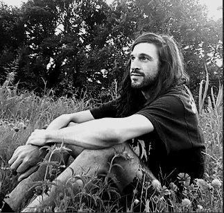A black and white photograph of the poet Brian Clifton. They are sitting in a field of wild flowers.