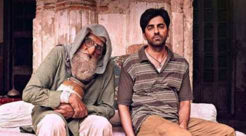 amitabh bachchan holding a jar of pickles and ayushman khurrana sitting on a cot in a still from the movie