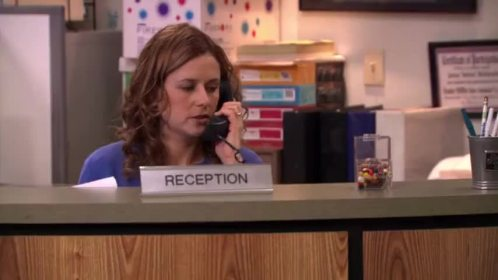 a girl talking on phone sitting at a reception desk