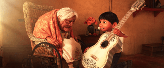 a boy playing guitar for an old woman sitting on chair