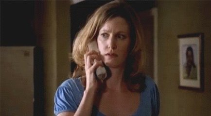 a woma talking on phone with an unusual expression on face