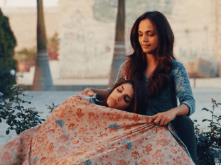 a woman sleeping with head in the lap of another woman and having a kashimiri shawl on her legs