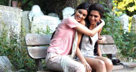 two girls sitting on a bench hugging each other