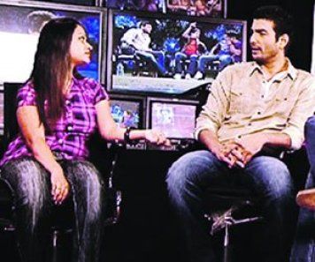 a girl sitting with a man in a room with many tv cameras set up