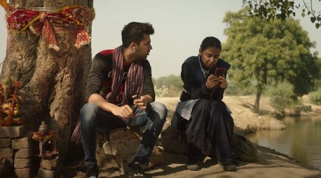 a girl and a boy sitting under a tree and watching something on a mobile phone and talking
