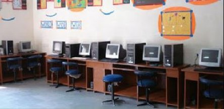 a computer lab with many coputer system set up and chairs