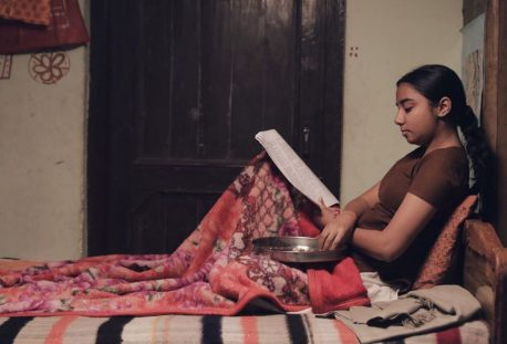a girl sitting on a bed with blanket on he legs reading a book