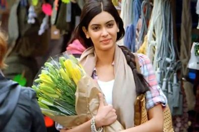 a girl carrying few flowers and smiling in a market place