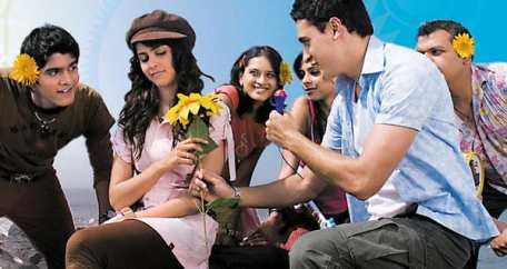 a group of 6 people holding sunflowers and giving a sunflower to the girl sitting in the center