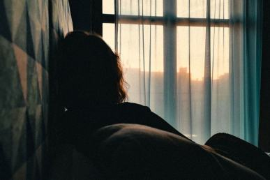 shadow of a woman sitting on the bed looking outside the window, showing the perks of living alone