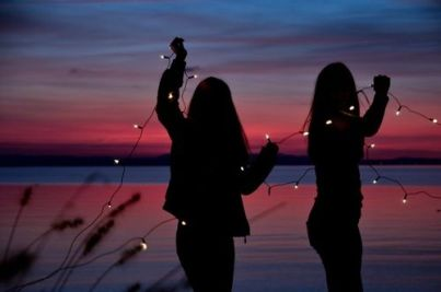 shadow of two girls holding fairy lights, at a sunset scene signifying female friendships