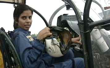 a pilot-gunjan saxena sitting in a helicopter holding her helmet