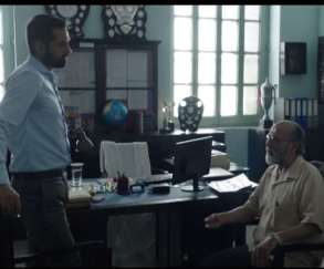 teo men talking, one sitting on a chair, scene from JL50
