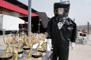 a statue wearing hazmat suit and standing next to a table of emmy awards 2020