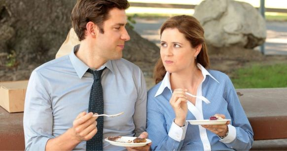 jim and pam from the tv show office sitting on a bench and eating something