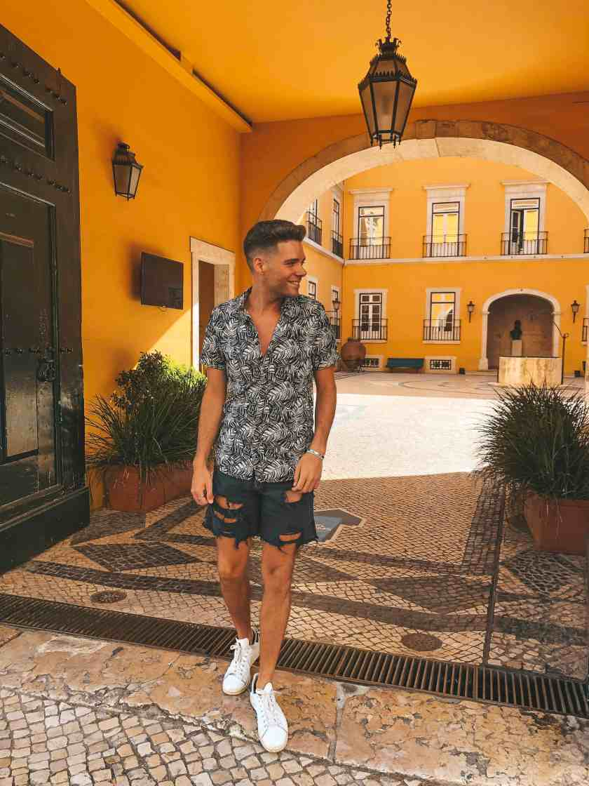 Adobe Lightroom Edited Image of young man in button down shirt and jean shorts walking in Portugal.