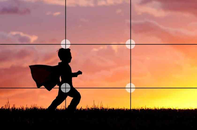 Photo of a young boy running on grass in sunset, with rule of thirds grid on image.