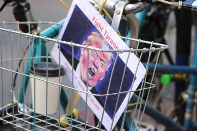 """""""Fight Tyranny sign with Trump's face on it in the basket of a bicycle"""" by Samantha Sophia on Unsplash"""