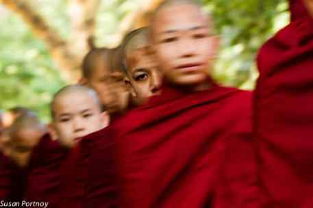 "Monks are fully sustained by the villagers. Here the monks walked in a single file line through their small town collecting food, or ""alms""."