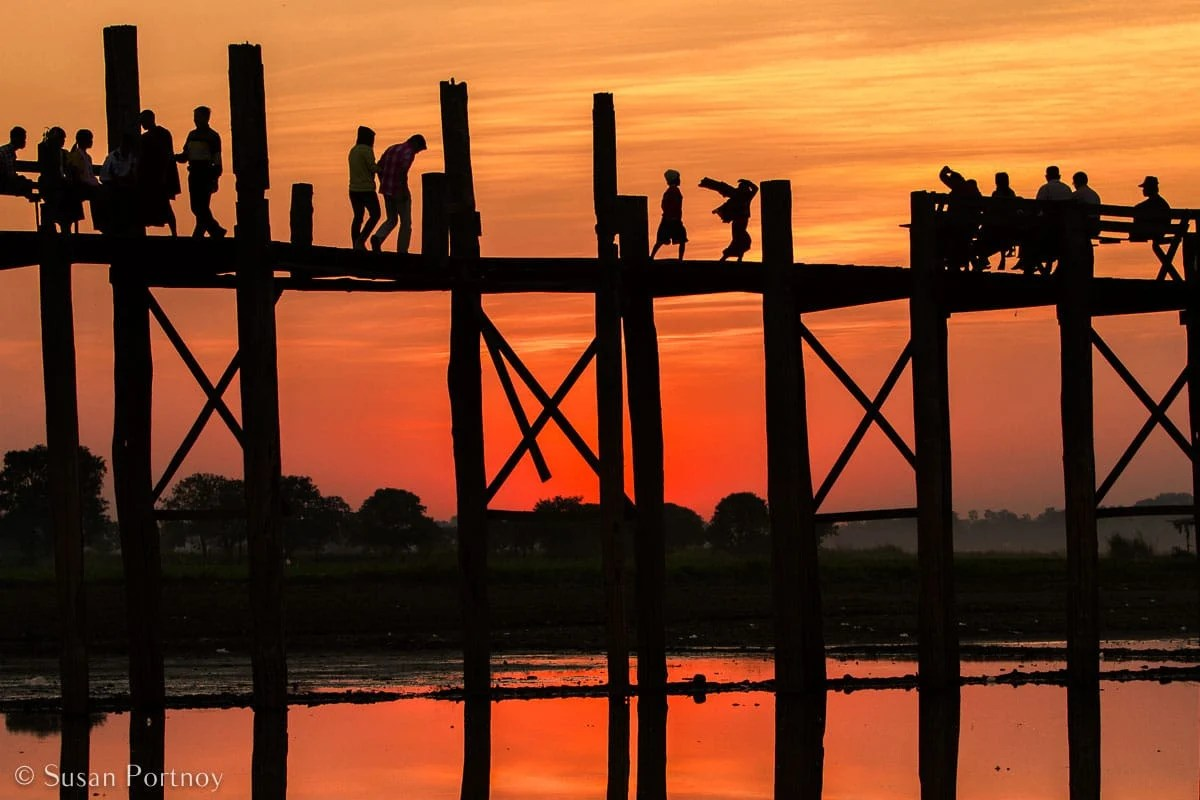 Stunning Silhouette Photos Guaranteed to Inspire Your Travels-Cut out from the background like paper dolls, travelers and locals cross the Ubein bridge in Mandalay, Myanmar