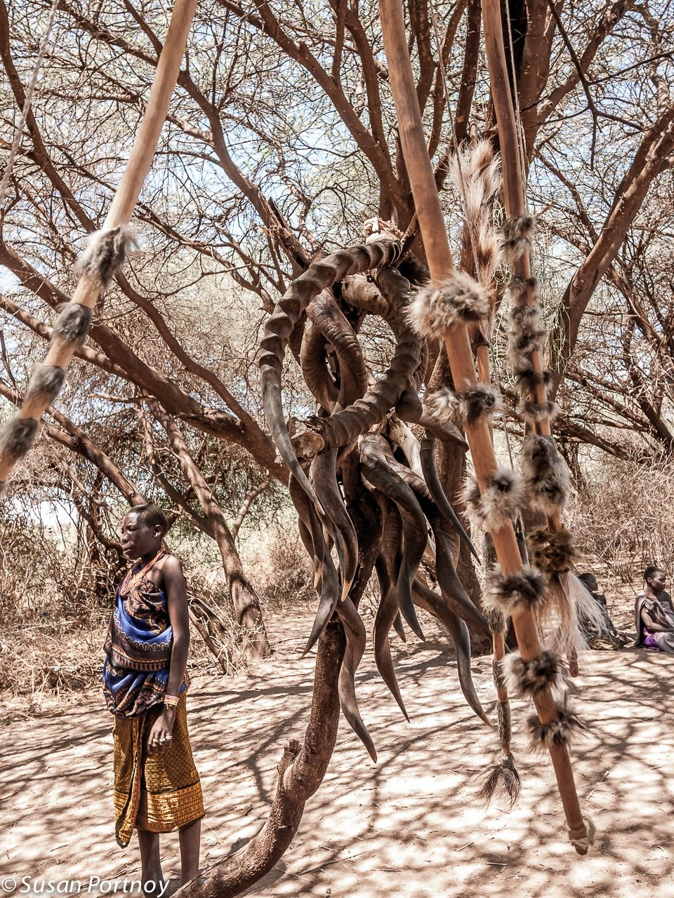 Hadzabe woman stands near impala horns in Tanzania