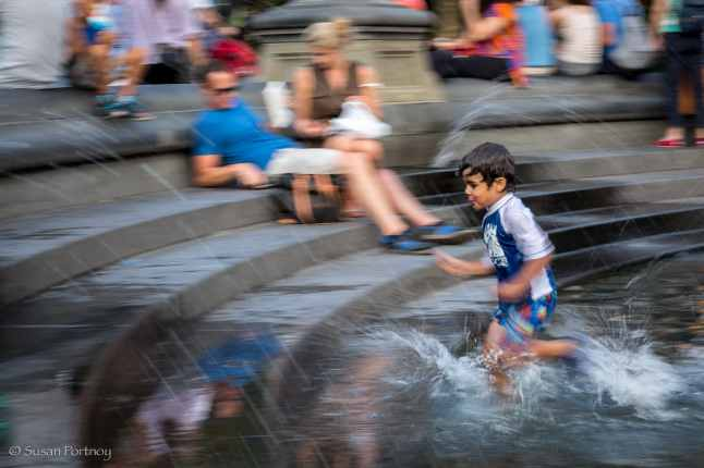 Little boy runs into the fountain in Washington Square Park, NYC