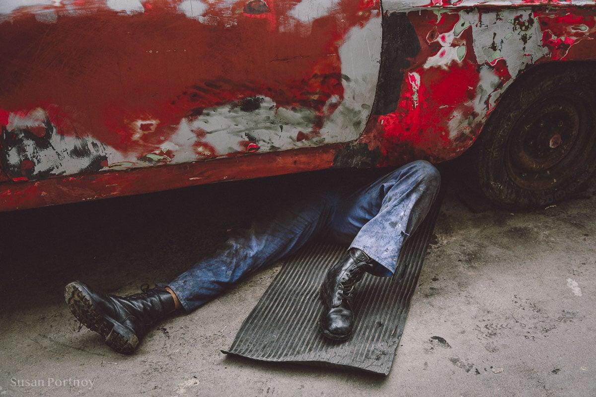 Man's legs from underneath a car in Havana
