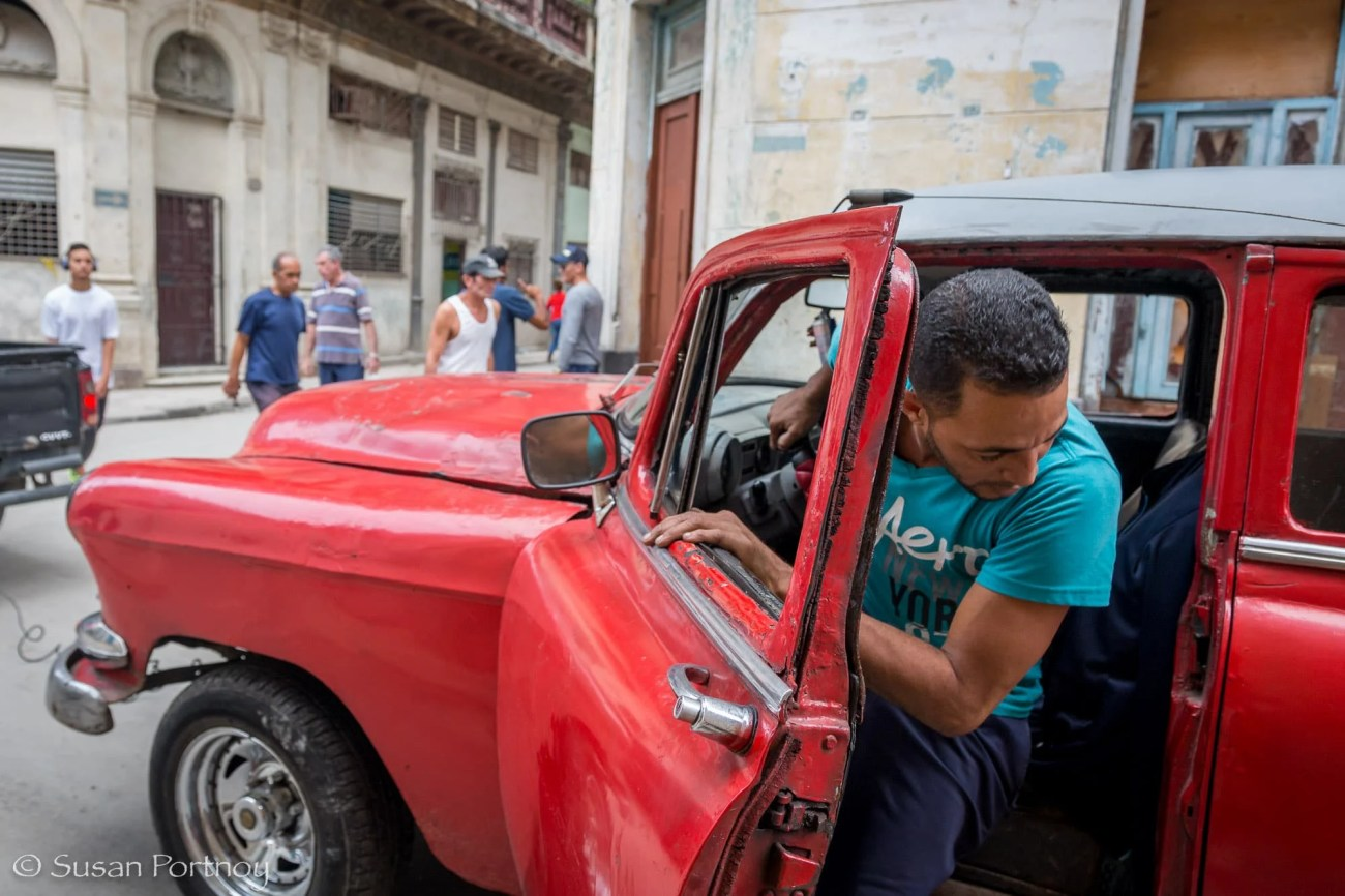 Man working on a beat up classic car driving in Havana, Cuba