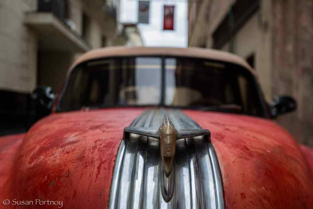 Red classic car with sexy hood ornament in Havana, Cuba