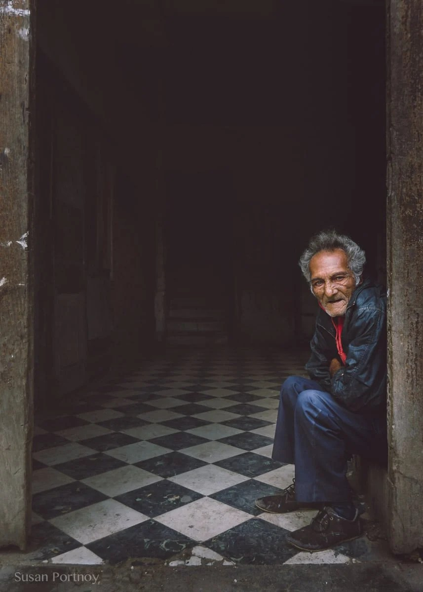 Photographing travel portraits of a man in a doorway in Cuba