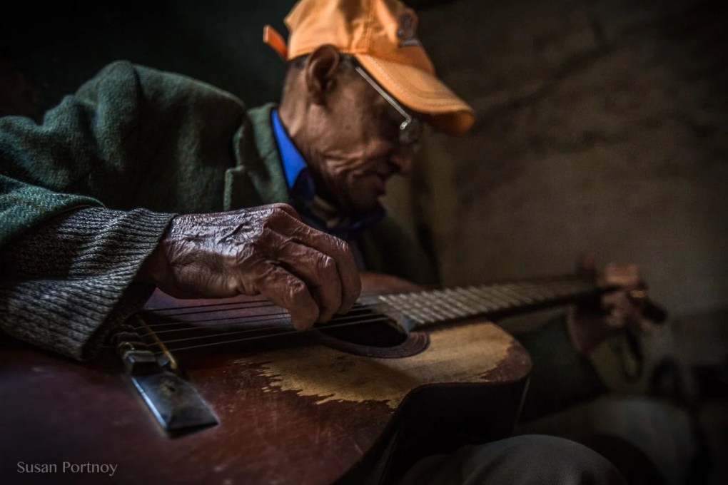 Photographing travel portraits of an old man playing guitar in Cuba