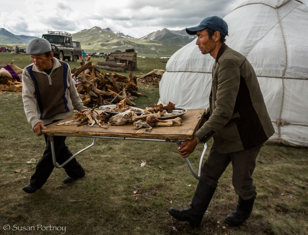 Men carrying food left over from a wedding in Altai Tavan Bogd National Park, Mongolia