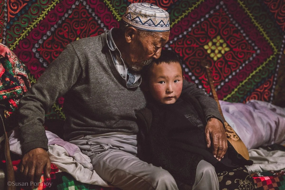 A sickly grandfather kisses the head of a young boy in mongolia