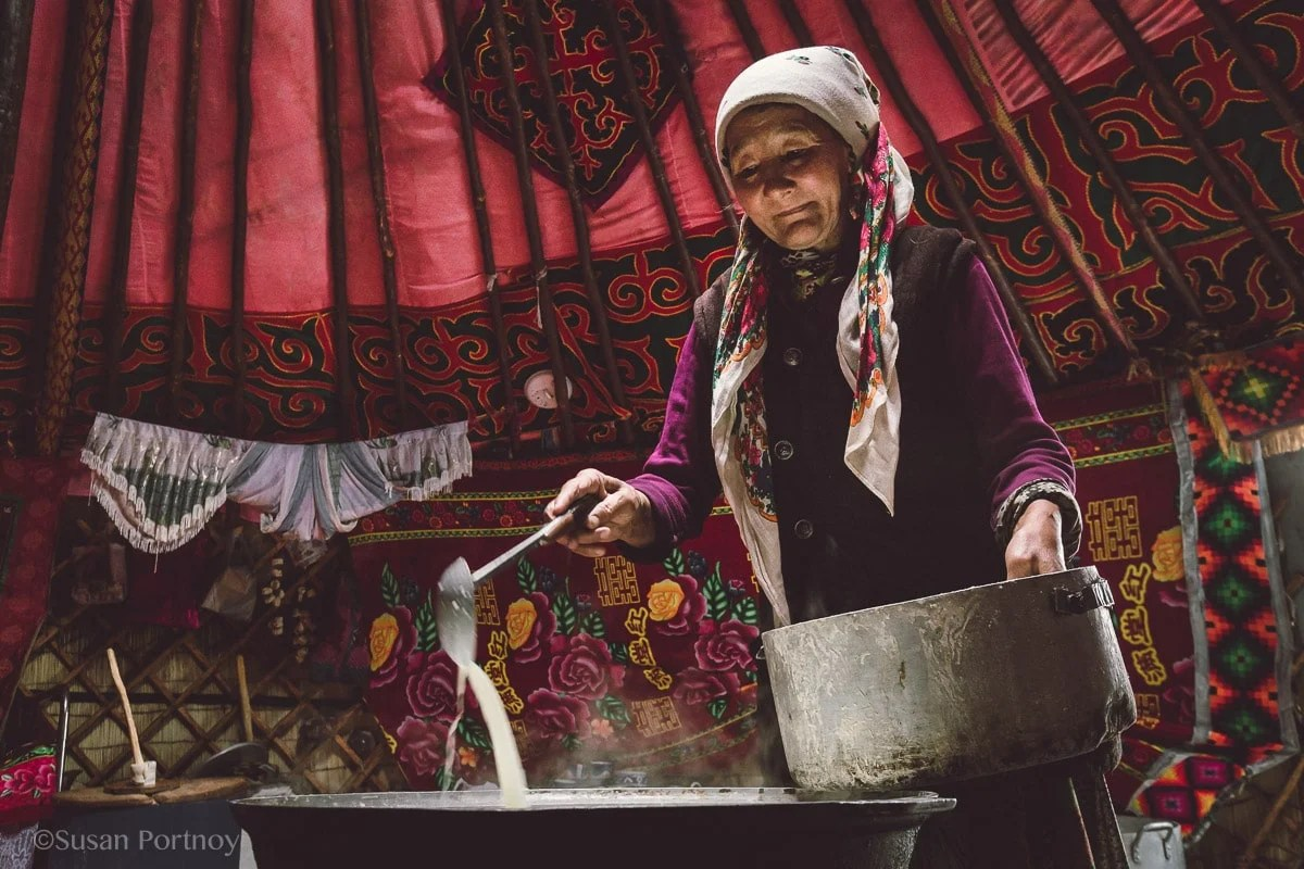 A woman adds more goat, sheep and cow's milk to a large metal pan on the wood burning stove that is will eventually be made into cheese Photographing Kazakh Nomads in Mongolia