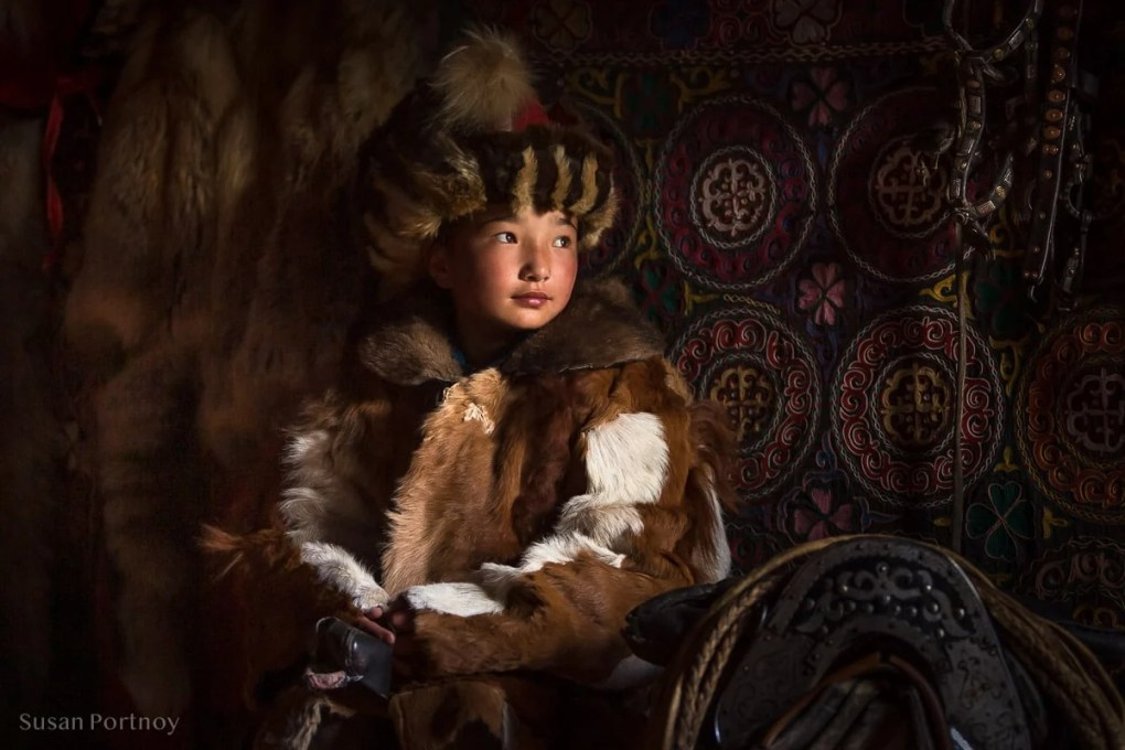 Sitting portrait of young Kazakh girl wearing traditional winter coat and hat next to a saddle and bridles