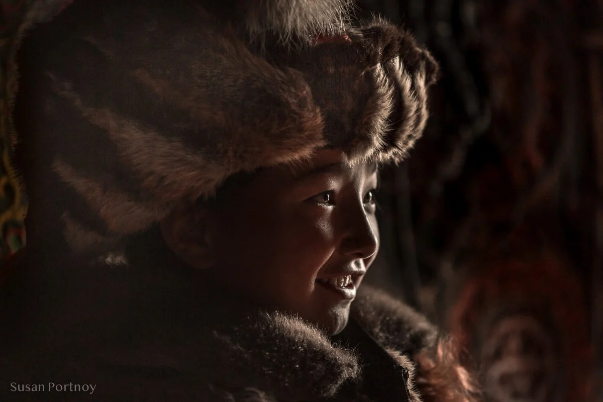 Sitting headshot of young Kazakh girl wearing traditional winter coat and hat, Altai Mountains, Mongolia